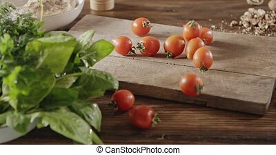 A woman throwing her hands of red cherry tomatoes on cutting...