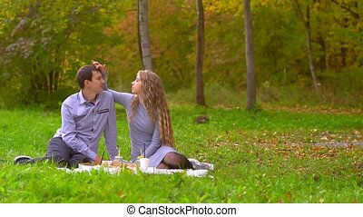 a woman touches a man in the Park on the lawn