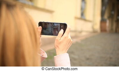 A woman tourist makes a photo of the city's attractions on her smartphone. Russia, Saint-Petersburg