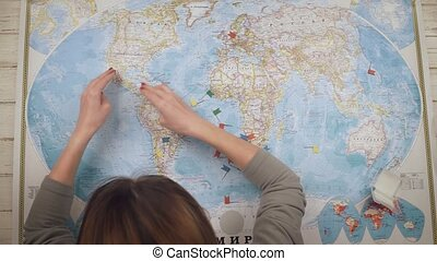 A woman traveler opens a map on the table and places flags in the cities of USA, Brazil, Argentina and Mexico where she wants to visit. Top view. Hands close up view
