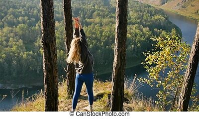 A woman traveler stands on the top of a mountain near the banks of the Mana River in Siberia and enjoys a beautiful view