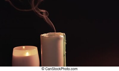A woman tries and extinguishes a candle on a black background. 2 burning candles, isolate. Romantic evening, the end of the holiday