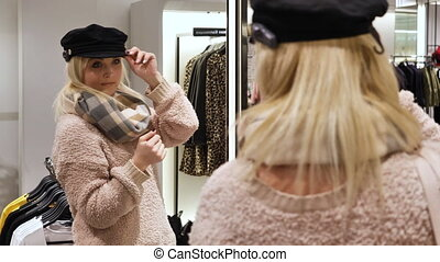 A woman tries on a hat with a visor near the mirror - Pretty...