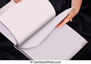 A woman two hands hold a empty book spread