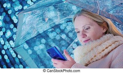 A woman under a transparent umbrella stands on a background...