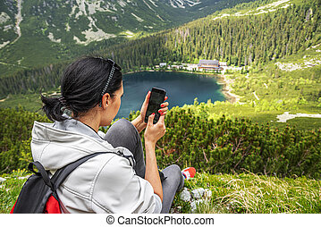 A woman uses a smartphone in the mountains while sitting on the edge of a cliff.