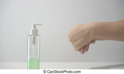 A woman uses hand sanitizer gel for clean hands to prevent the spread of coronavirus. Using rubbing alcohol instead of washing hands. Measures to prevent spread of covid-19 virus. Disinfecting hands.