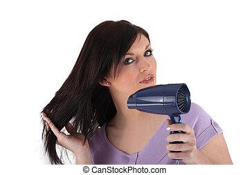 a woman using a hair dryer