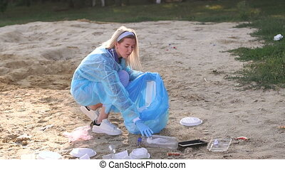 A woman volunteers picking up trash on the beach.