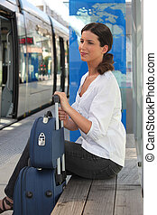 a woman waiting at tram station