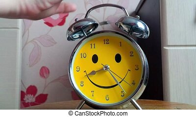 A woman wakes up and turns off her alarm clock.