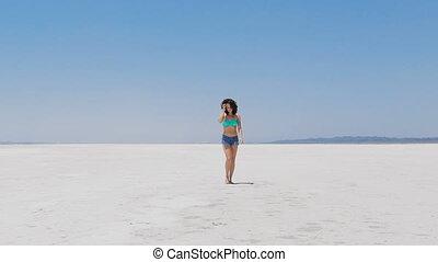 A woman walking at a very white salt lake in Cyprus