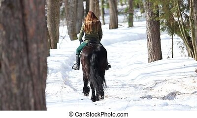 A woman walking on a horse in a winter forest on a snowy...