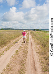 A woman walks along a country road in summer