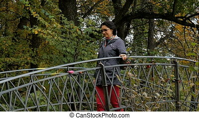 A woman walks in the park, going through the old bridge, sunny autumn day.