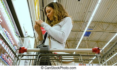 A woman walks with a cart and selects yogurt, puts in a basket in the supermarket, 4K.