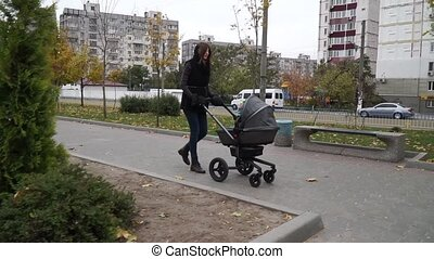 A woman walks with a stroller through the city