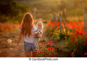 A woman walks with her back to the camera across a field of poppies and carries a child in her arms