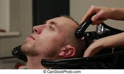 A woman washes her hair in the Barber shop bearded man with...
