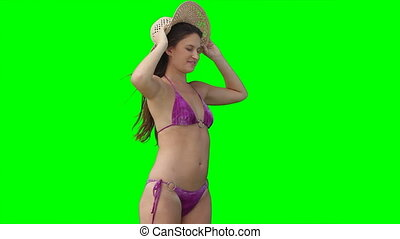 A woman wearing a hat as it is blown away against a green...