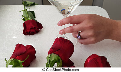 a woman wearing big violet diamond ring on her finger holds a glass with white vine