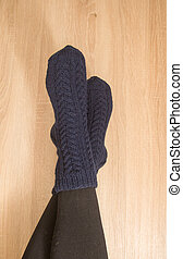 A woman wearing warm hand craft socks. Knitted form a natural sheep wool yarn. Winter clothing.