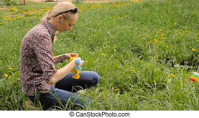 A woman weaves a wreath of dandelions. mother weaves a...