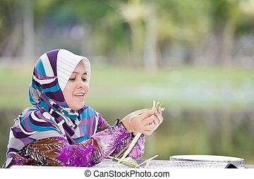 A woman weaving bamboo mats