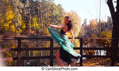 A woman with a blue stole in her hands dancing on the bridge alone