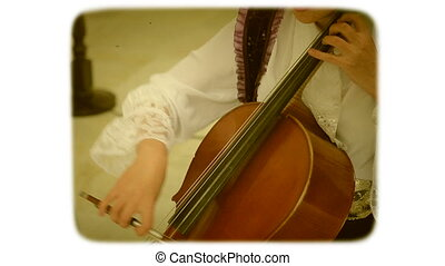 A woman with a bow drives the strings of a double bass. 8mm...