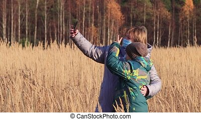 A woman with a boy in masks are photographed together on a smartphone