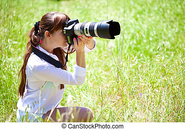 A woman with a camera in the field