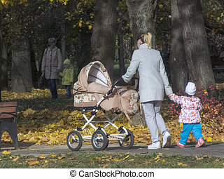 A woman with a child in the park walks. It is autumn