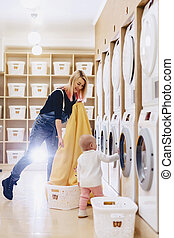 A woman with a child puts the sheets in the laundry