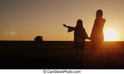 A woman with a girl admires the beautiful sunset in a...