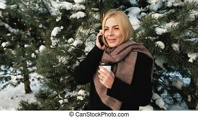 A woman with a glass in forest talking on the phone and smiling.