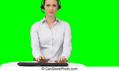 A woman with a headset typing on her keyboard