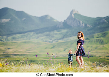 A woman with a little boy in the background of the mountains