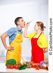 a woman with a wooden spoon feeds a man a healthy vegetable salad in the kitchen