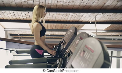 A woman with blond hair in the gym walks along the treadmill.