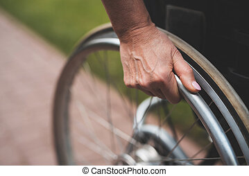 A woman with cancer is sitting in a wheelchair. She holds her hands behind the wheels of wheelchair on which she sits.