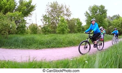 A woman with children riding bicycles in the park