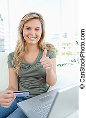 A woman with credit card in hand and laptop beside her, smiles giving a thumbs up.