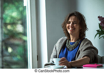 A woman with cup of tea sitting at a table near the window in her home.