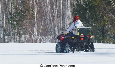 A woman with ginger hair in winter clothes riding snowmobile...