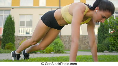 A woman with headphones trains standing on the grass in a plank performing a rock climber exercise in a slow-motion scheme in a city park. High quality 4k footage