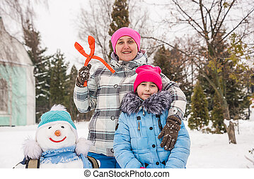 a woman with her daughter playing in the snow