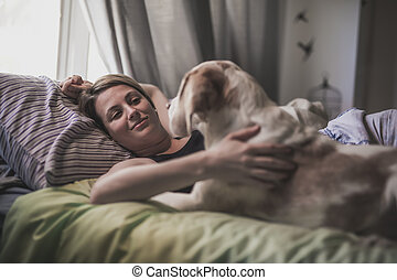 woman with her dog in the bed at home
