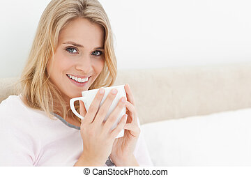 A woman with her head turned slightly and smiling, with a cup in her hands raised to her lips.
