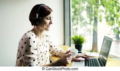 A woman with laptop and headphones sitting at the table in a cafe.